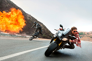 Tom Cruise on a motorbike runs away from bad boys on explosion background msmstudy.eu